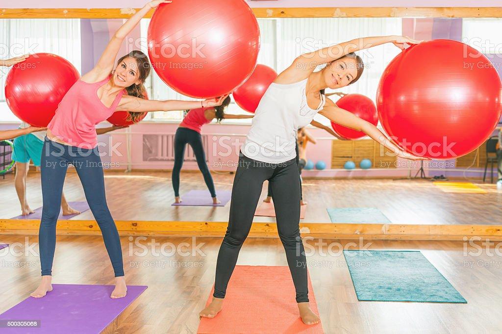 Beautiful multiracial women doing exercise with gimnastic ball. stock photo