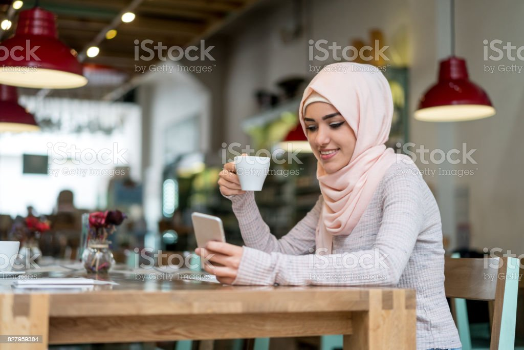 Beautiful Muslim woman at a cafe checking her cell phone stock photo