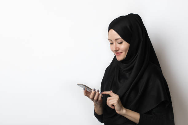 a beautiful muslim woman is looking at something on the phone, pointing her finger at the screen. - velo islamico foto e immagini stock