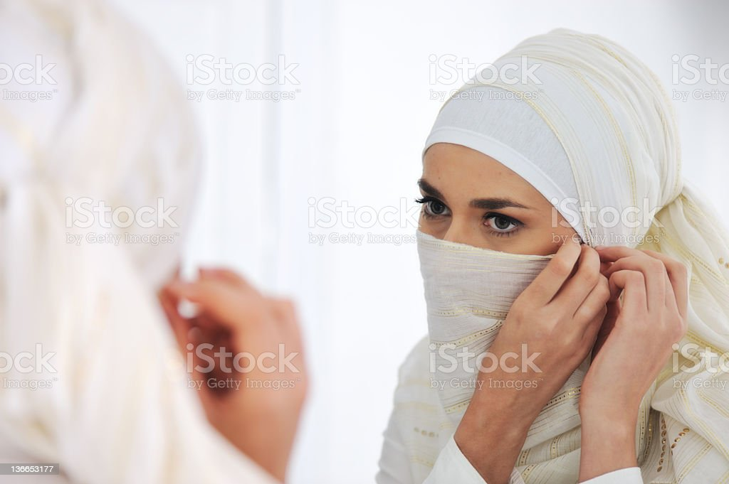Beautiful Muslim woman looking at mirror and putting her scarf stock photo