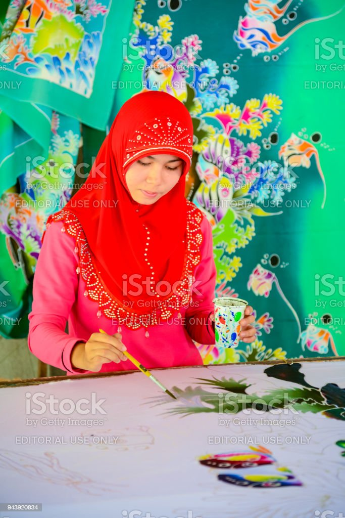 Beautiful Muslim woman painting pattern on Batik fabric stock photo