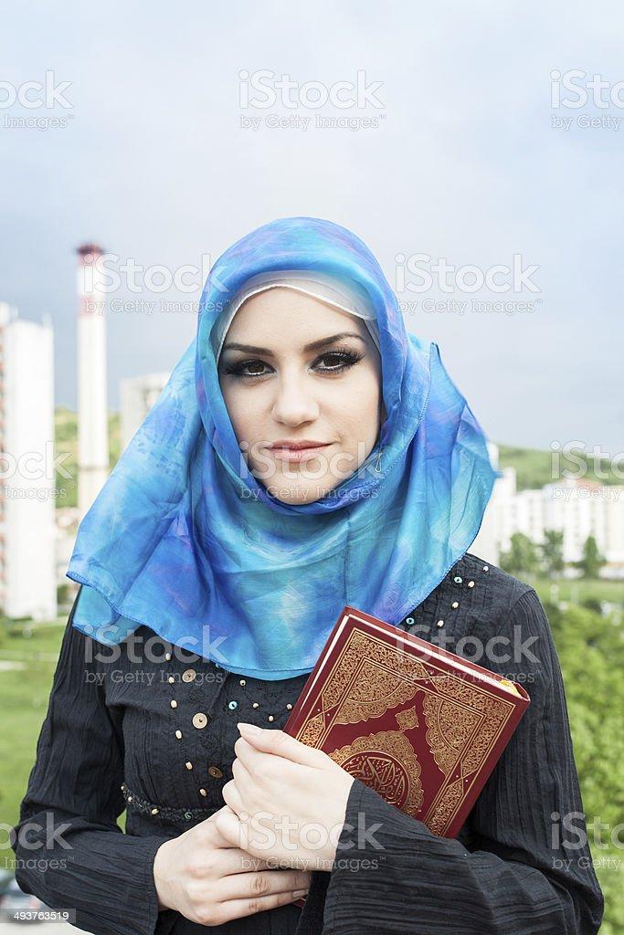 beautiful muslim woman wearing hijab and holding the Koran stock photo
