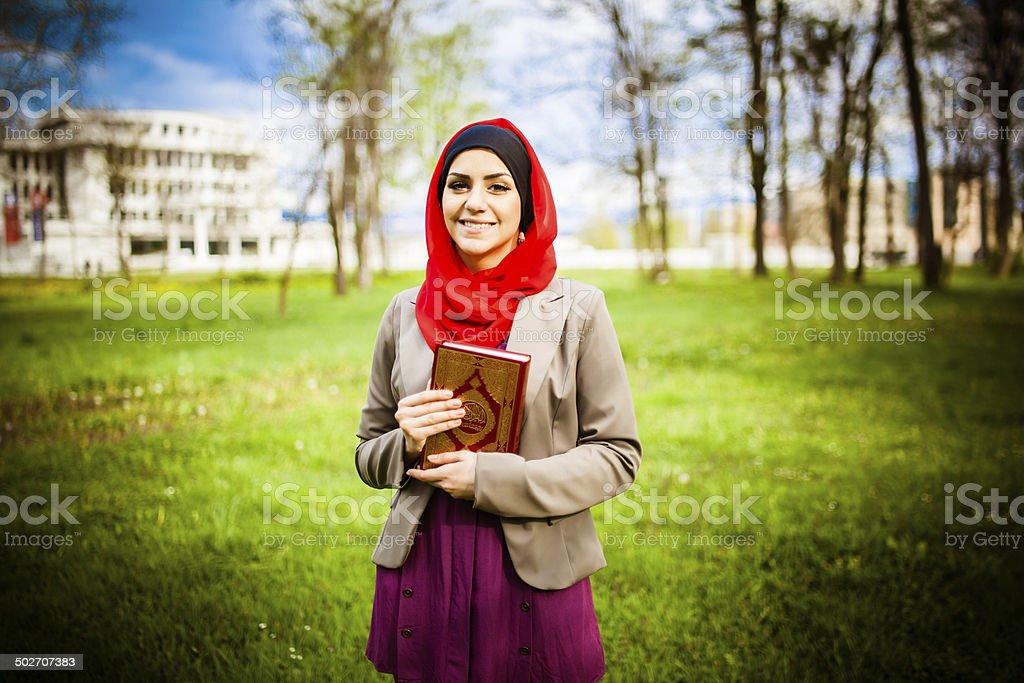 beautiful muslim woman wearing hijab and holding the Koran royalty-free stock photo