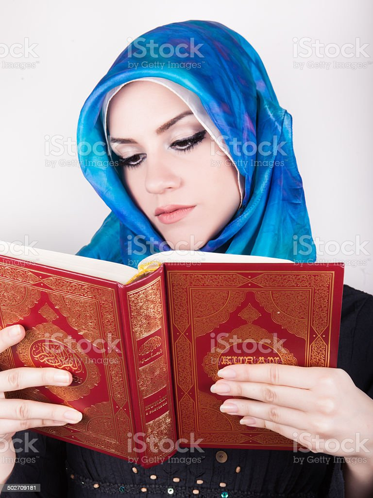 beautiful muslim woman wearing hijab and reading the Koran royalty-free stock photo