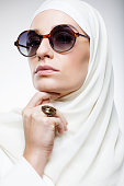 Beautiful caucasian Muslim Woman wearing white hijab and sunglasses in luxury studio shot