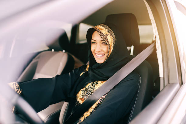 beautiful muslim woman with toothy smile driving car. - saudi woman stock photos and pictures