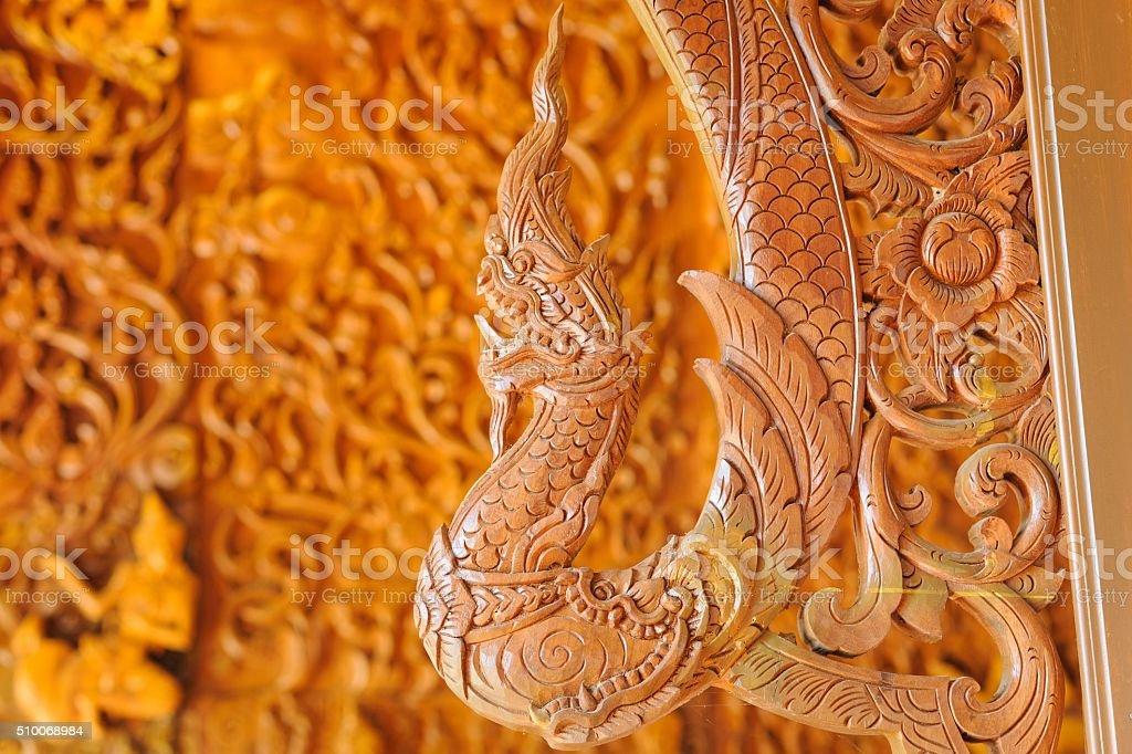 Beautiful Naga teak wood carving sculptures in Thai temple. stock photo