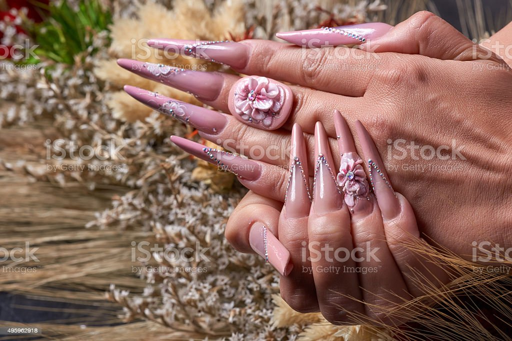 fashionable woman with long acrylic nails with 3d paint on...