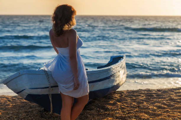 Beautiful naked  female in the pareo near boat on the sand stock photo