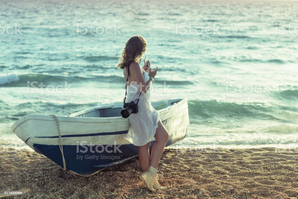Beautiful naked  female photographer in the pareo with professional camera near boat on the sand stock photo