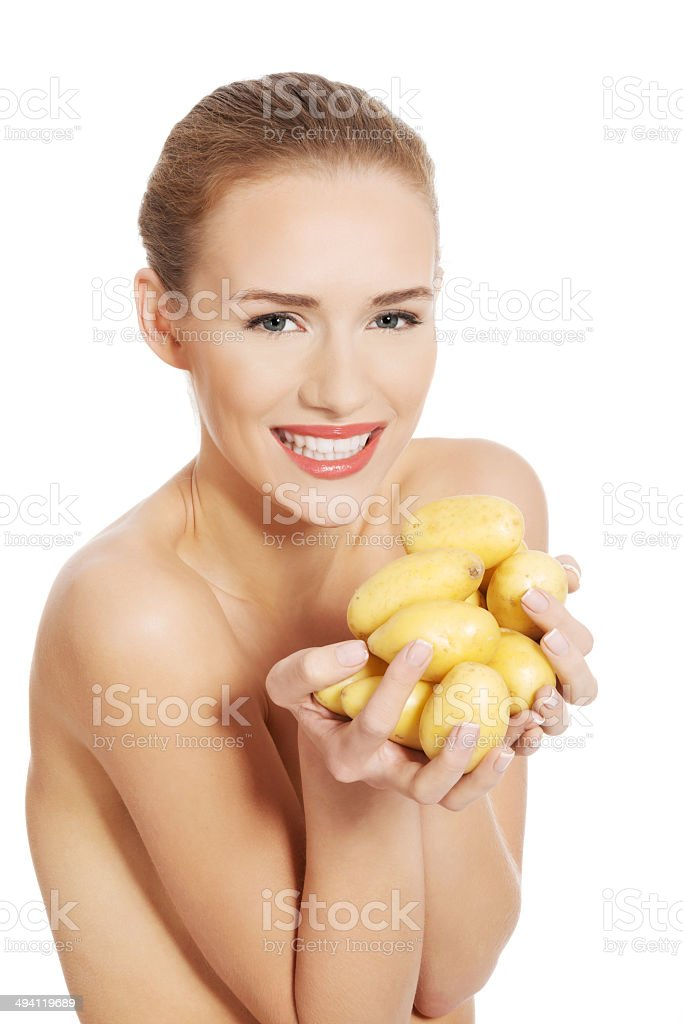 Beautiful naked woman holding raw potatoes in hands. stock photo