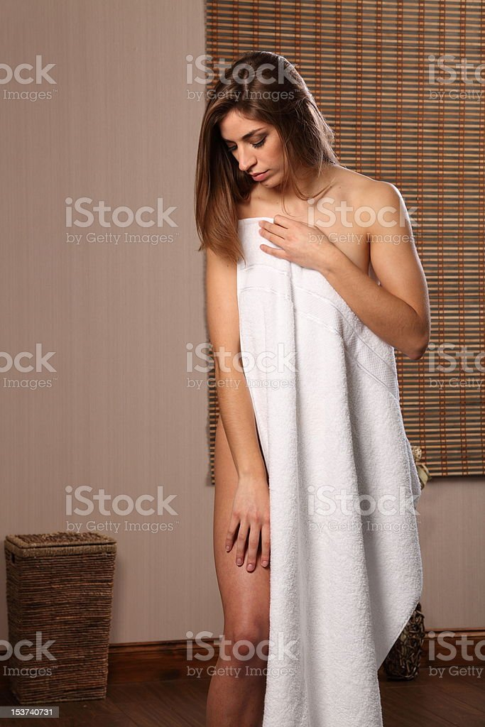 Beautiful naked woman holding white towel over her body stock photo
