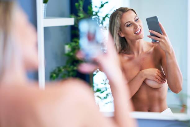 mooie naakte vrouw met smart phone in de badkamer - cell phone toilet stockfoto's en -beelden