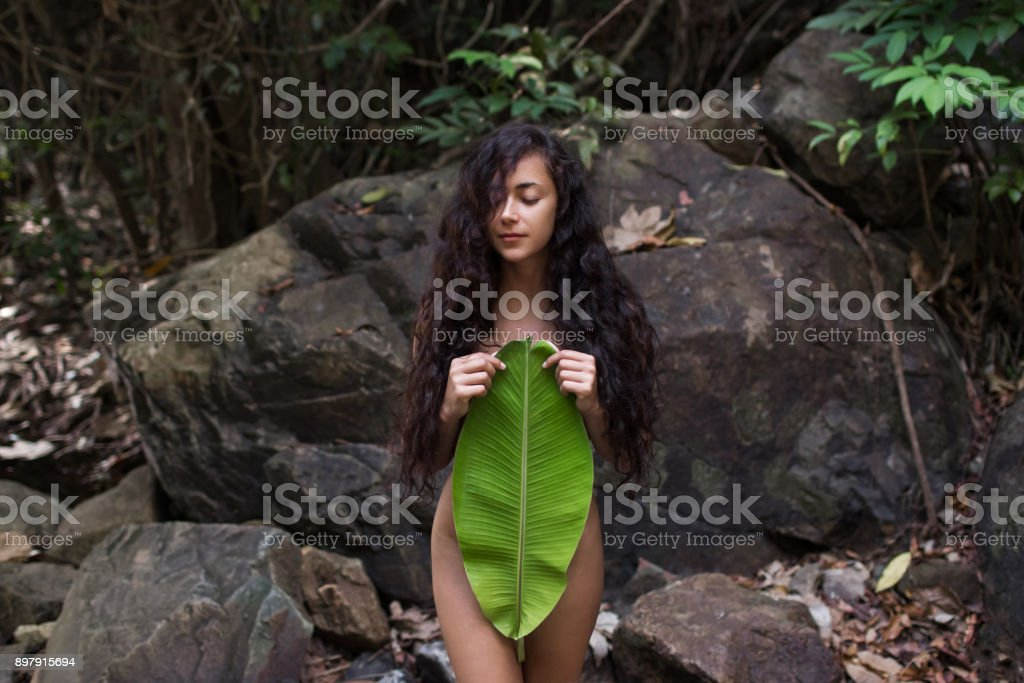 Beautiful Naked Young Woman In Jungle With Palm Leaf Stock