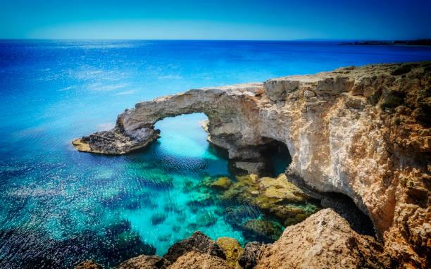 beautiful natural rock arch near of ayia napa, cavo greco and protaras on cyprus island, mediterranean sea. legendary bridge lovers. - cyprus стоковые фото и изображения