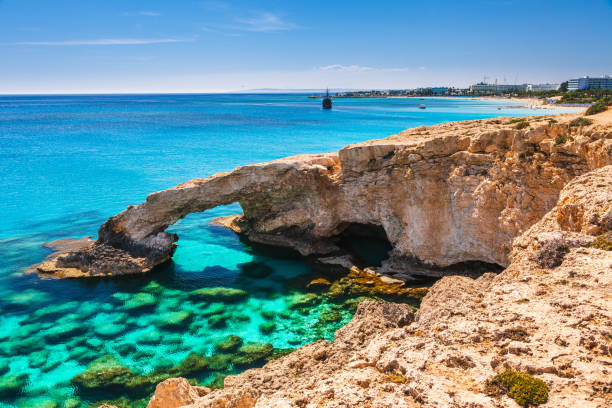 beautiful natural rock arch near of ayia napa, cavo greco and protaras on cyprus island, mediterranean sea. legendary bridge lovers. amazing blue green sea and sunny day. - cyprus стоковые фото и изображения