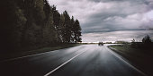 Moody landscape with dark storm clouds, forest, car and road out of horizon. Beautiful nature background and wallpaper
