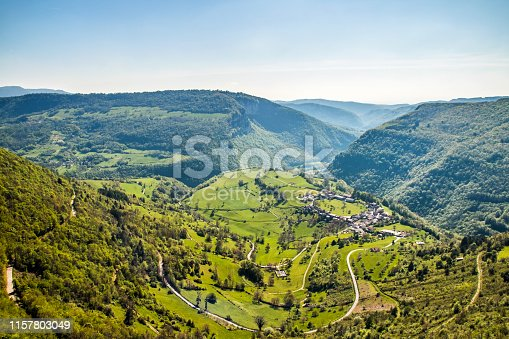 Vibrant color photography of beautiful small old village in circle shape wide view, in middle of French countryside in Bugey mountains in spring season. This image was taken in France in Ain, Auvergne-Rhone-Alpes region, with small village of Oncieu.