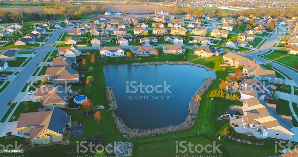 Beautiful neighborhoods, homes around pond, aerial view, Springtime dawn. stock photo