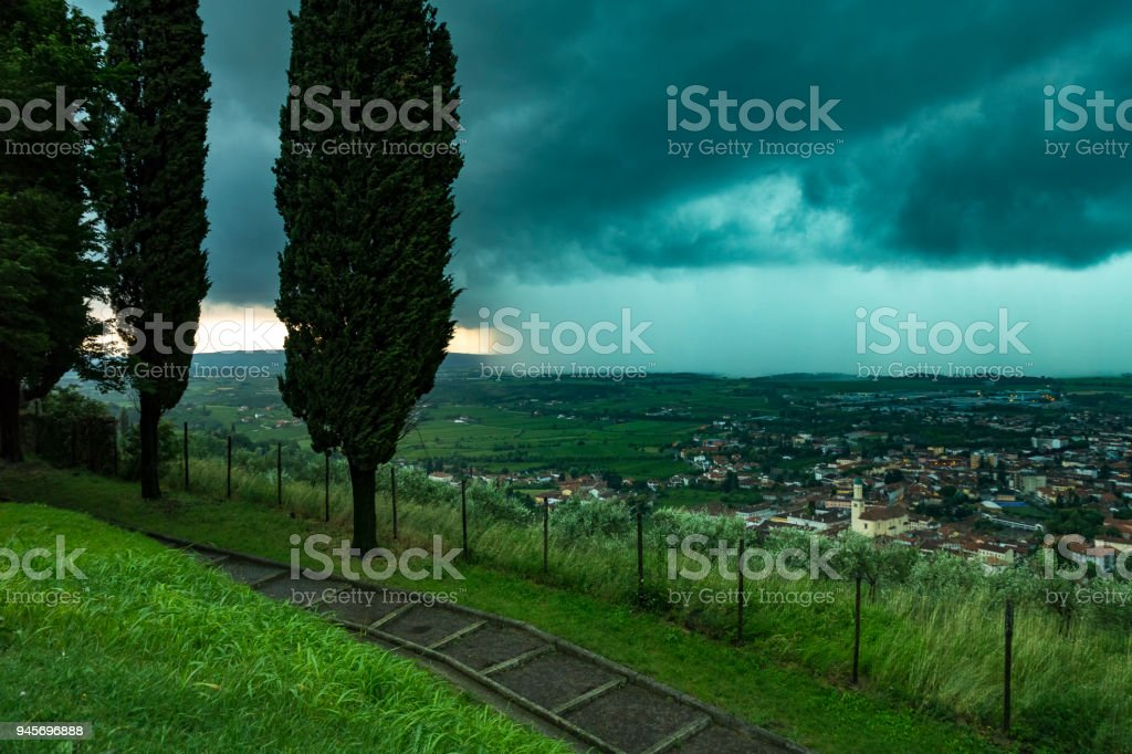 Beautiful neon tinged storm cloud bringing torrential rain to the city of Cormons stock photo