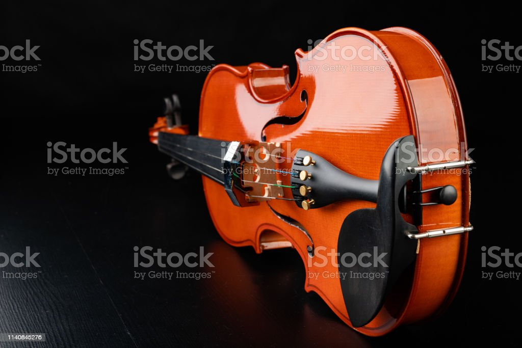 Beautiful new shiny violin on a dark table. Musical string instrument...