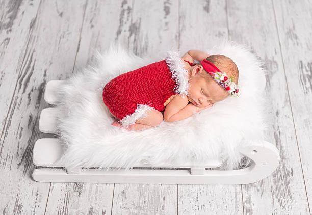 beautiful newborn in red romper on sleigh cot - baby born schlitten stock-fotos und bilder