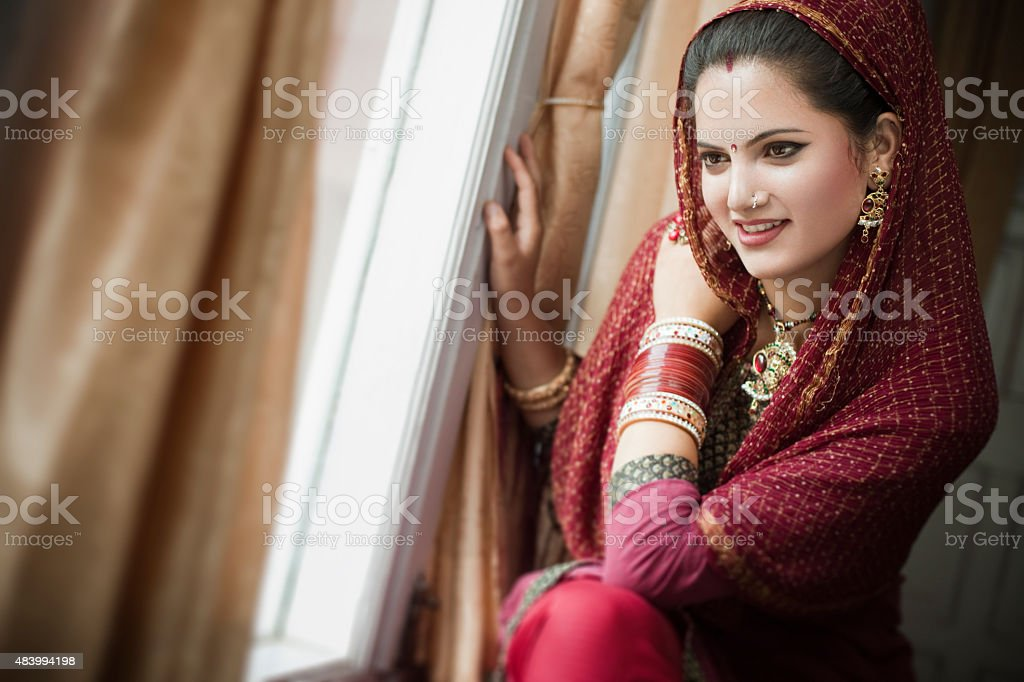 Beautiful newly married happy Indian young woman sitting near window. stock photo
