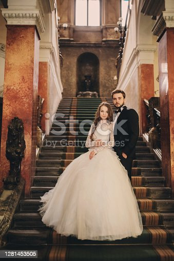 Beautiful newlyweds hugging on stairs the ancient house. Wedding portrait of a stylish groom and a young bride inside.