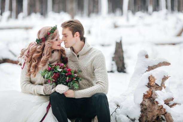 wunderschöne brautpaar im winterwald. moment, bevor ein kuss. kunstwerk - strickmantel stock-fotos und bilder