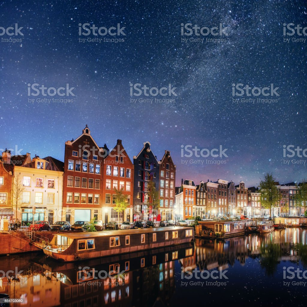 Beautiful night in Amsterdam. Night illumination of buildings and boats near the water in the canal. stock photo