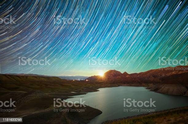 Photo of Beautiful night landscape. Lake, mountains, moonrise and strartails on the sky.