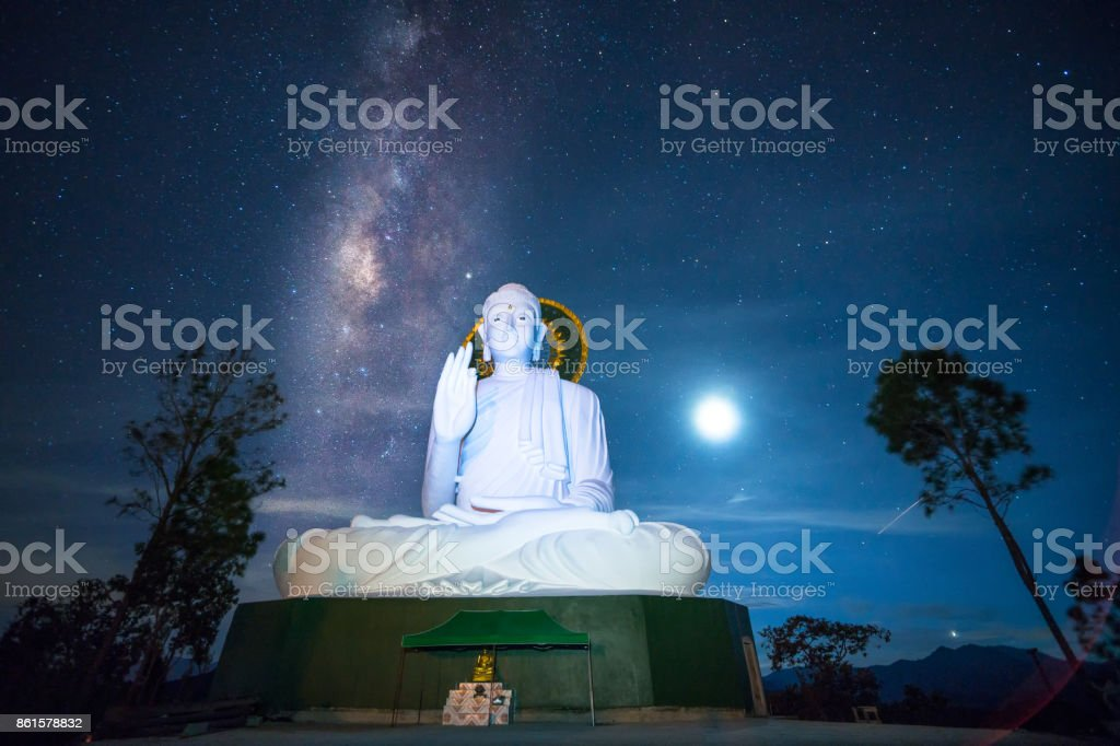 Beautiful night sky with milky way over big Buddha statue in one temple of Chiang Rai Thailand. Long exposure has noise and grain. stock photo