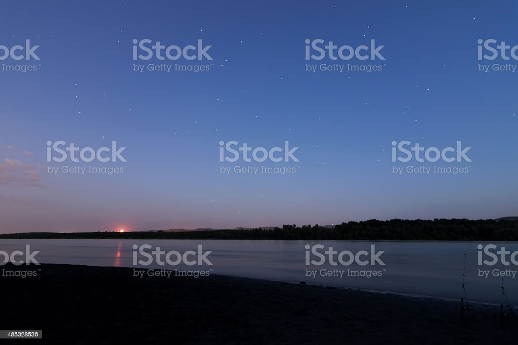 Beautiful night sky with moon and constellation over Danube river stock photo