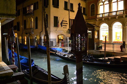 Beautiful night view to a Venice canal with gondolas anchored.
