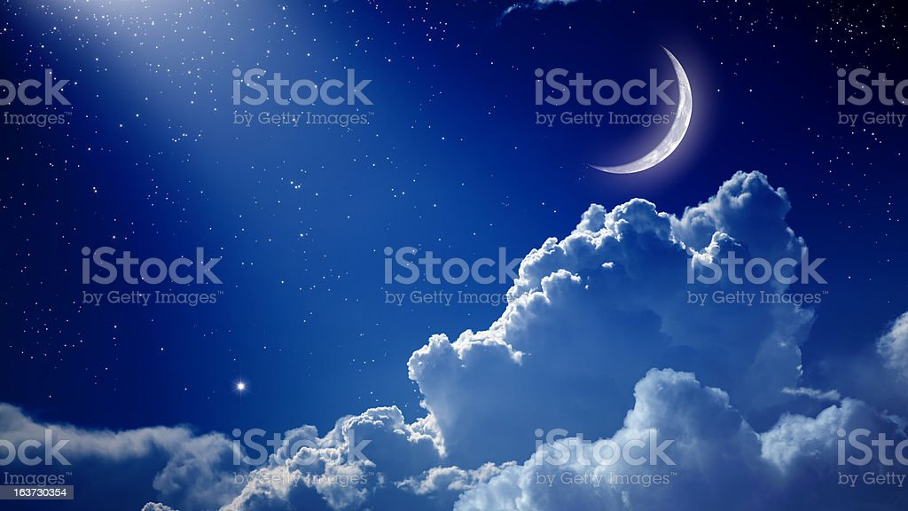 A beautiful night with a blue sky, the moon, and clouds stock photo