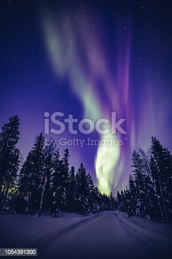 istock Beautiful Northern Lights (Aurora Borealis) in the night sky over winter Lapland landscape, Finland, Scandinavia 1054391300