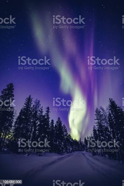 Photo of Beautiful Northern Lights (Aurora Borealis) in the night sky over winter Lapland landscape, Finland, Scandinavia