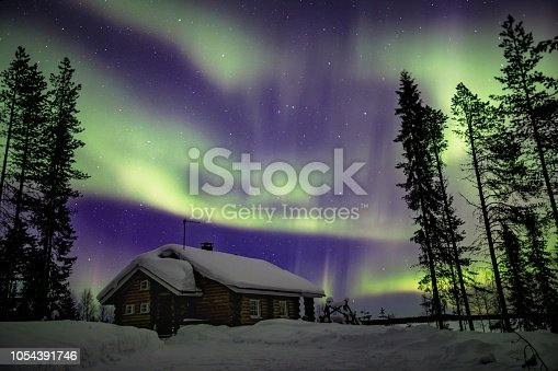 istock Beautiful Northern Lights (Aurora Borealis) in the night sky over winter Lapland landscape, Finland, Scandinavia 1054391746