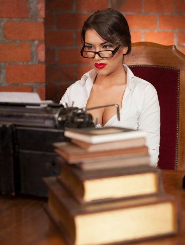 Beautiful  woman writer sitting in front of large desk and typing on the old typewriter. Old styled image