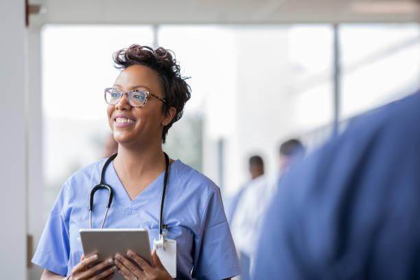 Beautiful nurse smiles while holding digital tablet stock photo