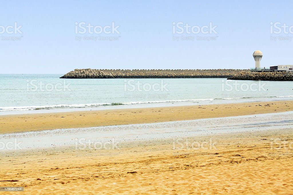 Beautiful ocean shore with lighthouse on the cape royalty-free stock photo