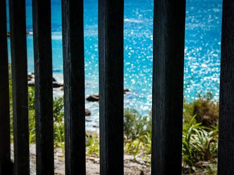 A beautiful ocean sparkles behind bars, symbolizing being trapped or imprisoned