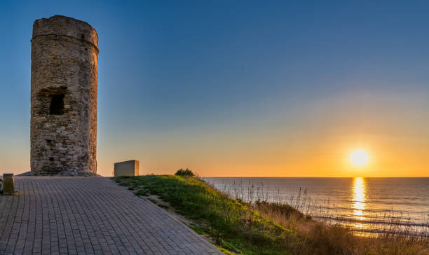 Beautiful ocean sunset near Torre del Puerco, a historic watch tower in Chiclana de la Frontera, Andalusia, Spain. - foto de stock