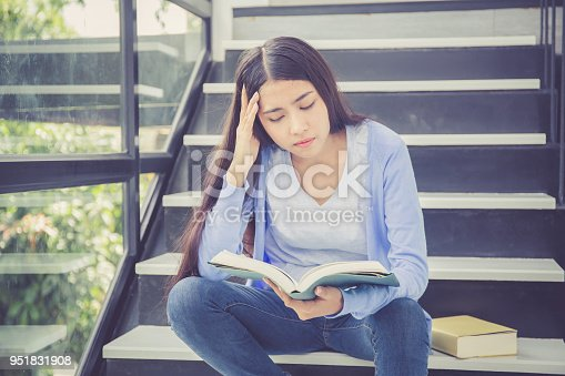 istock Beautiful of portrait asian young woman holding book, girl tired and bored reading book studying for exams, education and lifestyle concept. 951831908