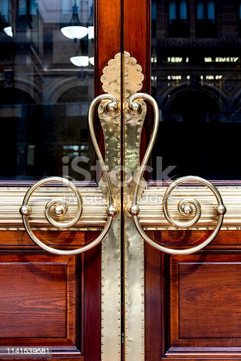 Beautiful old door brass handles, background with copy space, full frame vertical composition