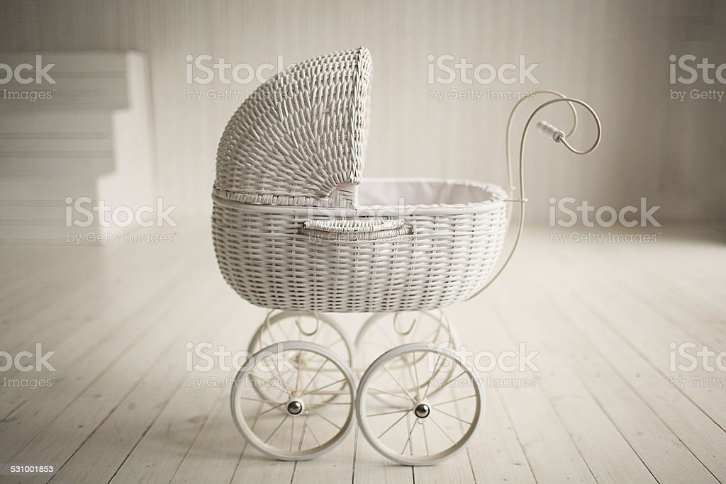 Beautiful old fashioned white pram in white room stock photo