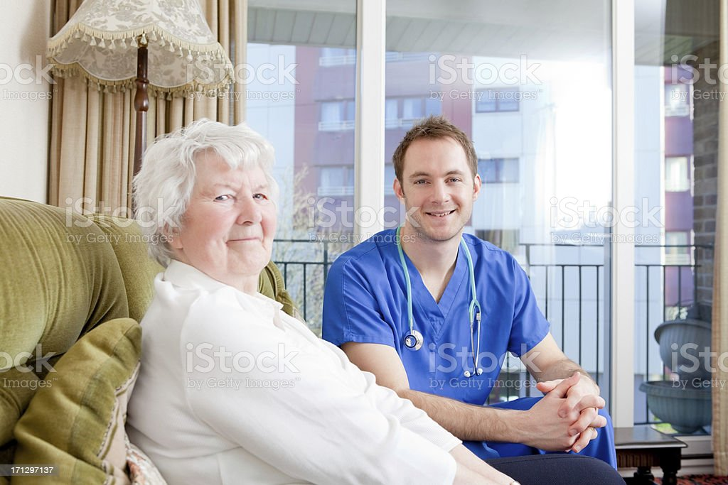 Beautiful old female patient with male nurse stock photo