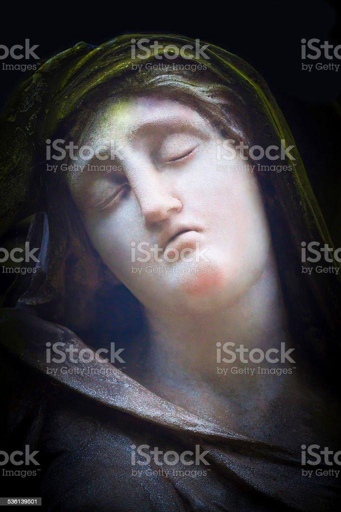 Beautiful old statue of Mary Magdalene isolated on black background stock photo