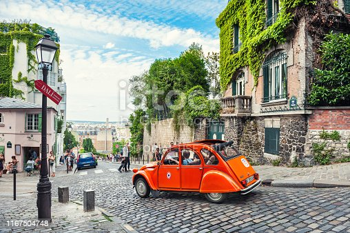 Paris, France - July, 21, 2019: Beautiful old street in Montmartre district in Paris, France. Orange retro car goes down the street.