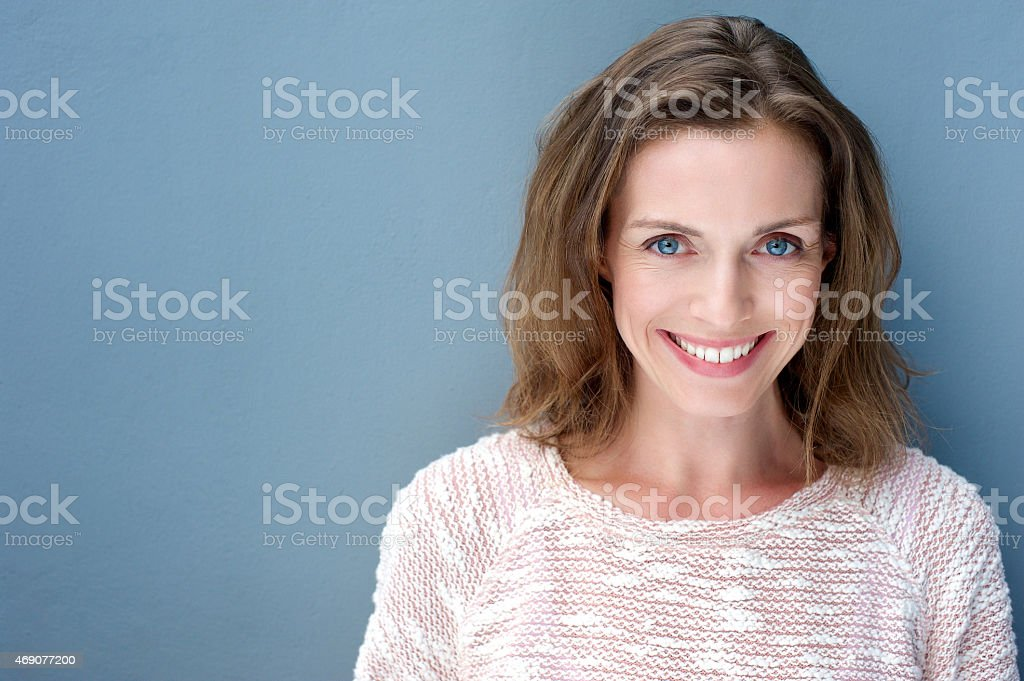 Beautiful older woman smiling with sweater stock photo